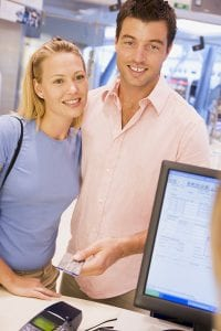 Couple making purchase with credit card in store
